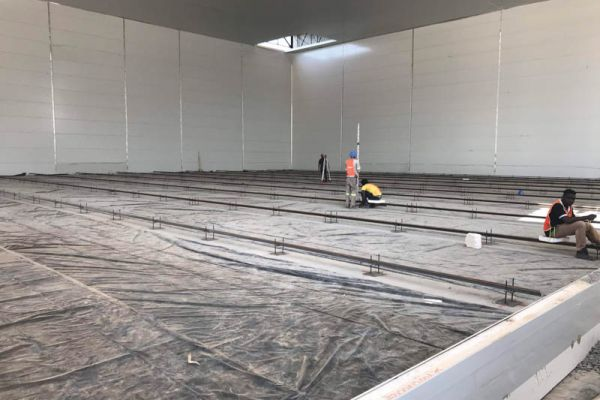 Tracks for mobile racks are installed into the foundation work.